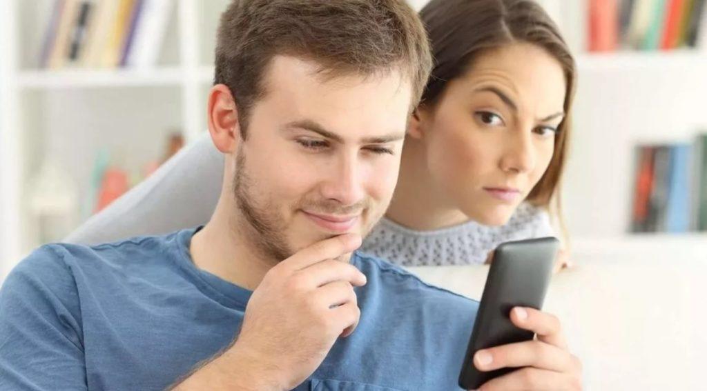 девушка смотрит переписку в телефоне у парня